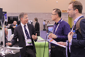 An exhibitor speaks to two meeting attendees
